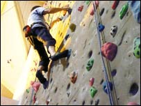 Person climbing up an indoor climbing wall