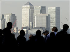 City workers silhouetted in front of Canary Wharf's skyline