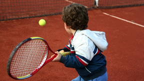 Young boy hitting a backhand on a tennis court.