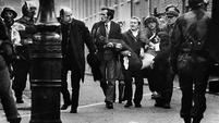 Father Edward Daly leads a group of people carrying the mortally wounded Jackie Duddy, waving a white handkerchief