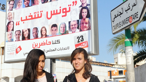 Tunisian students pass in front of a poster of election candidates