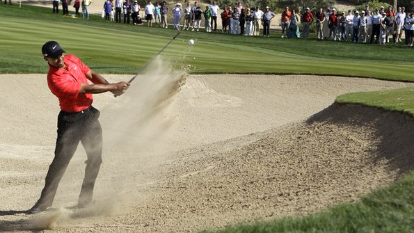 Tiger Woods plays a shot from a bunker