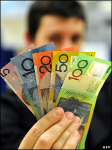 A shopper brandishes Australian dollar banknotes in Sydney