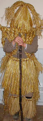Fermanagh mummer complete with a three pronged straw pleated hat, straw jacket and straw skirt