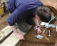 an archaeologist digging and recording a find