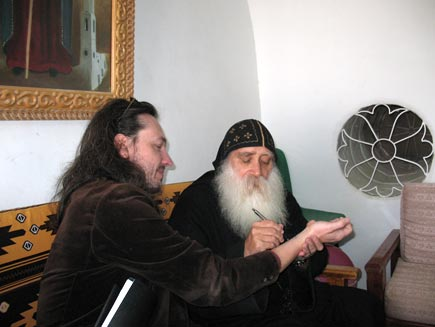 Father Ruwais, a Coptic monk wearing black robes and skull cap and a long white beard, sits drawing on Nicholas Buxton's arm. The monastery room contains wooden furniture and a round patterned glass window with a painting of a saint visible on one of the white-painted walls