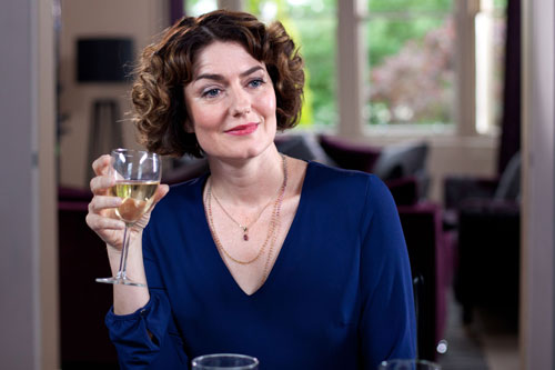 Laura's mum (Anna Chancellor) drinks a glass of wine