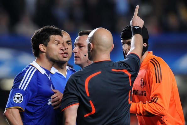 Chelsea players argue with referee Tom Ovrebo
