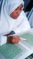 A girl wearing a white gown and Muslim headscarf and digital watch reads the Qur'an