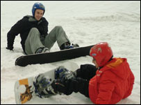 Two people trying to snowboard
