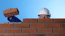 Builder adding a brick to a wall
