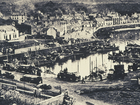 Black and white view of harbour with fleet of fishing boats and a number of loaded trucks on the quayside.