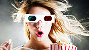 A girl wearing 3D glasses eating popcorn
