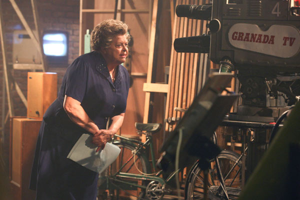 Lynda Baron as Violet Carson sits by an old camera in The Road To Coronation Street