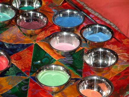 Polished bowls full of coloured sand are arranged on a colourful cloth by the edge of the mandala table