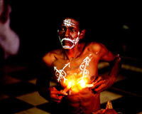 Shirtless dark-skinned man with symbols drawn on his face and body in bright white, holding lit candles against his chest