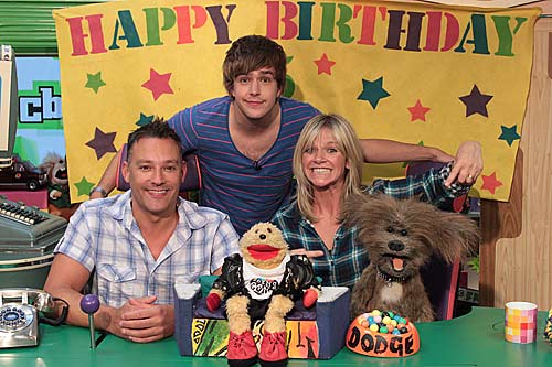 Toby Anstis, Iain Stirling and Zoe Ball celebrate the 25th anniversary in the CBBC Broom Cupboard