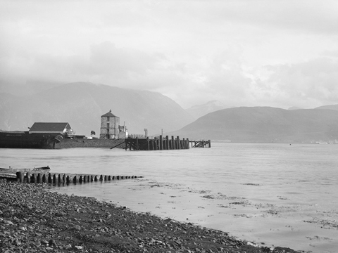 Black and white view from a rocky beach across Loch Linnhe to Ben Nevis. In the middle distance is a quayside featuring a tall, masonry constructed building and a wooden pier.