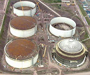 Aerial picture of the five storage tanks built to keep the gas chilled, with CGI showing the top of one