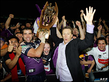 Melbourne Storm captain Cameron Smith (L) holding the National Rugby League (NRL) trophy aloft with coach Craig Bellamy (R) on 30 September 2007