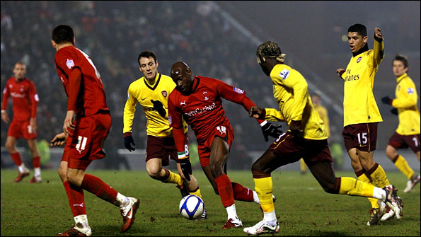 Jonathan Tehoue moves away from a posse of Arsenal defenders