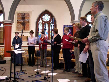 The Daily Service Singers, nine men and women wearing ordinary clothes, stand in a semicircle around small microphone stands inside the church.  Christian-themed wall hangings and stained glass windows can be seen in the background