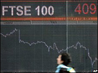 Woman walks past display screen of FTSE 100 index