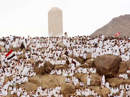 Mountain on the plain of Arafat where dozens of people  dressed in white sit in contemplation and prayer