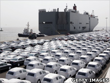 New cars, covered with white protection sheets, wait to get loaded onto transport ships at the Volkswagen car factory Emden on 24 April 2009