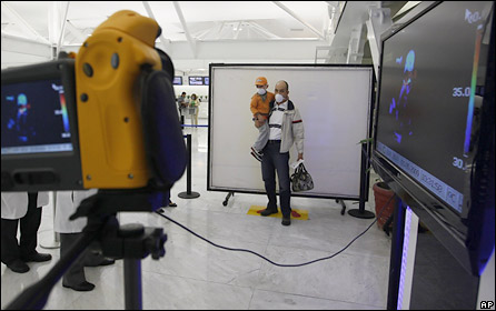 "A thermal scanner records the temperature of a man and a child, as a precaution against the swine flu outbreak, before they board a plane at Mexico City""s airport, Friday, May 1, 2009"