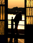 Silhouette of a person leaning on a railing during a sunset, thinking