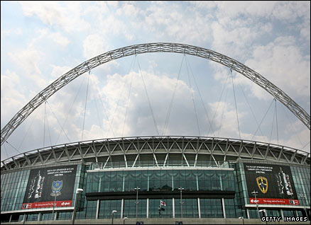 The logos of Portsmouth FC and Cardiff City FC hang on the side of Wembley stadium in preparation for the FA Cup final