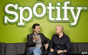 founders Martin Lorentzon (L) and Daniel Ek talking in front of a giant Spotify logo