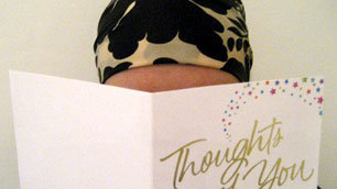 Lisa, wearing a headscarf, is partially obscured as she reads one of the many Get Well Soon cards she received