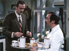 A still from the 1970s sitcom 'Fawlty Towers'. Hotel owner Basil Fawlty examines trays of food being carried by waiter Manuel.