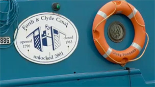 Side of a blue barge with an orange lifebelt and a plaque stating Forth and Clyde canal. Unlocked 2001.