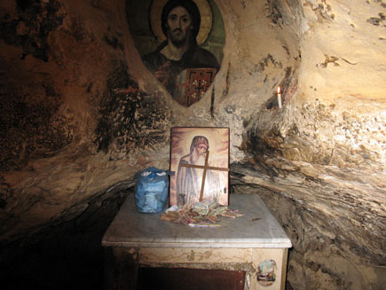 Inside the cave a small table serves as altar, with a plastic bag of papers, a pile of monetary donations, a painting of Saint Antony and a simple wooden cross.  On the wall behind, seeming to be painted directly on the stone, is a larger picture of Christ.  A small white candle burns in a niche in the rock