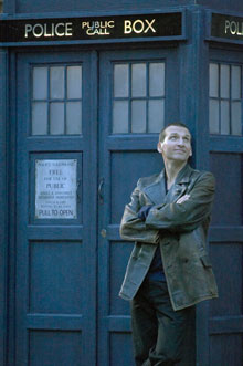 The Ninth Doctor Christopher Ecclestone standing outside a TARDIS
