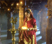 Hindu girl in temple holding lamp near gold statue