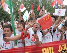 People cheer during the Olympic torch relay in Hefei, central China on 28 May 2008
