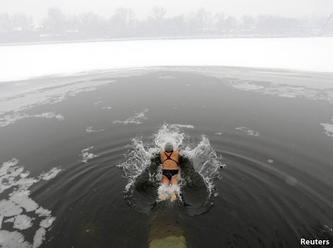 Swimmer plunging into a frozen lake