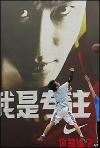 Boys playing basketball in front of advert of Liu Xiang