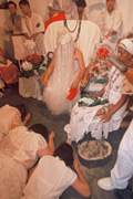 Man sitting on chair with his head covered by silver fringe all the way to the floor. Female worshippers prostrate before him