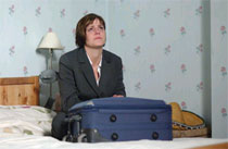 a female character sitting with a suitcase and crying