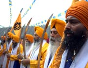 Sikh men in turbans with swords in a festival procession