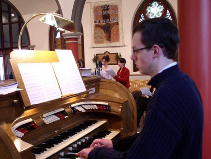 Greg Morris the organist sitting at the console of a small Conacher organ, with the choir members nearby in the background