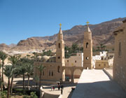 Sand-coloured buildings in the desert with Christian crosses atop two towers