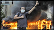Smoke billows from a burning bus as a supporter of defeated Iranian presidential candidate Mir Hossein Mousavi flashes the victory sign during a protest in Tehran on June 13, 2009