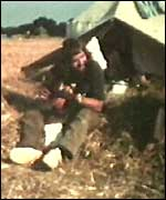 Man playing the guitar outside a tent