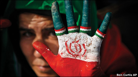 A female supporter of Iranian President Mahmoud Ahmadinejad displays her hand painted with the Iranian flag, also used as a sign for his party